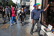 Man wearing a multicoloured umbrella hat selling little window climbing wall crawlers as people pass by on Tottenham Court Road in London, England, United Kingdom.