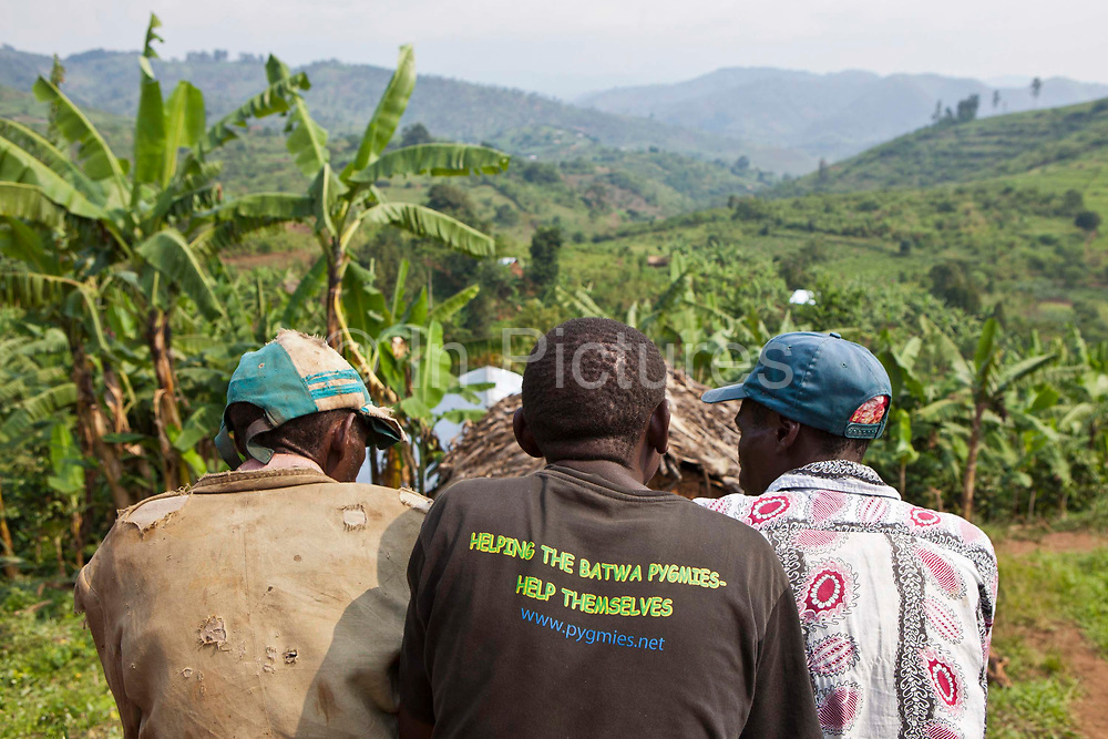 Local men from the Batwa tribe community discuss issues as they gather for a funeral of Matale, a local woman who died of cancer.