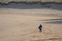 ©2020 Tom Nicholson. 23/04/2020. Padstow, UK. A bodyboarder walks along the beach shortly after sunrise this morning near Padstow on the north coast of Cornwall. A period of warm weather is set to continue for the rest of the week. Photo credit : Tom Nicholson