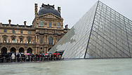 """Rain falls as visitors wait to enter the Musée du Louvre in Paris, France on May 19, 2012.  It was """"museum night"""" throughout Europe, so admission was free."""