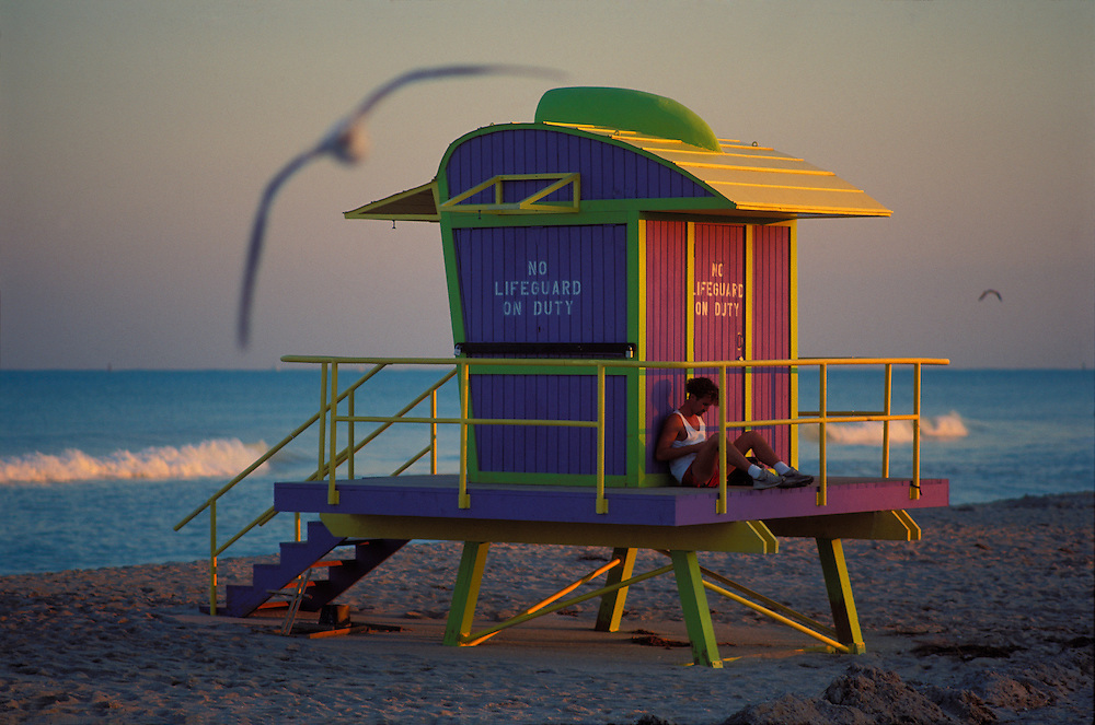 At dusk, seagulls swirl past a solitary man sitting on a whimsical, bird-like, post-modern lifeguard stand designed by architect Bill Lane for the City of Miami Beach