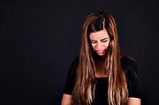 Crying teen studio shot on black background