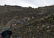 Tourists climb up the steep terraces of Ollantaytambo's Inca ruins.