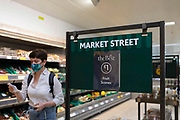 A woman wearing a face mask passes a sign for Market Street, the fresh produce section, inside popular British supermarket chain Morrisons on 23rd August, 2021 in Leeds, United Kingdom. British supermarket chain Morrisons, which employs over 110,000 staff across its 500 shops, has accepted a £6.3bn $8.7bn takeover bid from US private equity firm Fortress Investment Group.