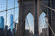 Skyscrapers of Manhattan viewed through piers, wire supports and cables of Brooklyn Bridge, New York City