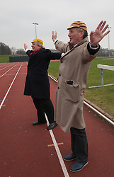 """© Licensed to London News Pictures. 03/03/2012. London, England. L-R: Terry Jones and Michael Palin doing warming up exercises. Terry Jones and Michael Palin of Monty Pythons fame today, Saturday 3 March, staged a public """"Hopathon"""" to mark the DVD release of Ripping Yarns The Complete Series, and as an homage to the episode entitled Tomkinson's School Days at the Athletics Track in  Hampstead Heath, London. Photo credit: Bettina Strenske/LNP"""