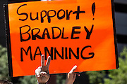 """06 JUNE 2012 - PHOENIX, AZ:   A supporter of US Army PFC Bradley Manning holds up a sign on a street corner in Phoenix Wednesday. About 10 people gathered on a street corner in central Phoenix Wednesday to support Manning, who been criminally charged for passing secrets in the """"wikileaks"""" case and is awaiting trial in a US Army jail.       PHOTO BY JACK KURTZ"""