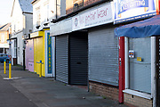 On the last day of the year, independent shops on York Road in Kings Heath remain closed, with shutters down due to Tier Four coronavirus restrictions on 31st December 2020 in Birmingham, United Kingdom. Small businesses have struggled through the Covid-19 pandemic and many have closed down altogether, as the recession in the economy deepens as the crisis continues.