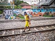 30 MAY 2013 - BANGKOK, THAILAND:    A man walks down the railroad tracks near Bobae Market in Bangkok.    PHOTO BY JACK KURTZ