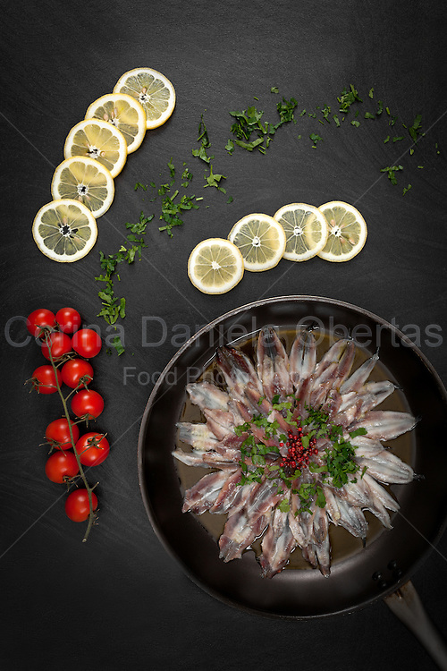 Pan with marinated anchovies with lemon, parsley, olive oil and peppercorns. Black background, top view shot.