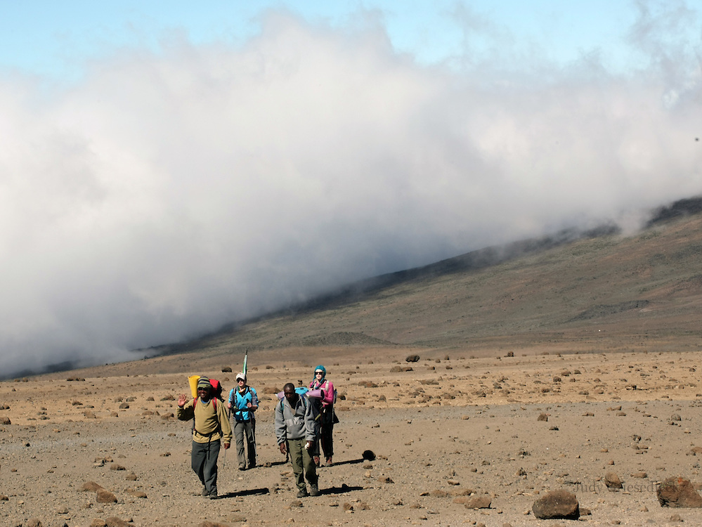 With clouds rolling along behind them, climbers up Mt. Kilimanjaro hike along towards the summit on Day three of the climb.