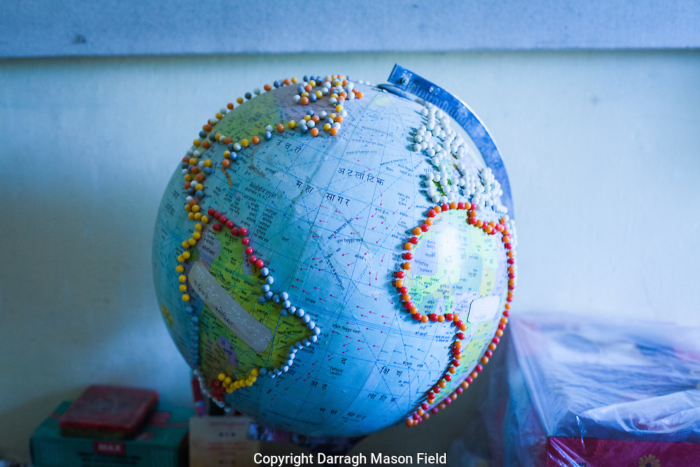 A globe with the outline of the continents raised with pins.