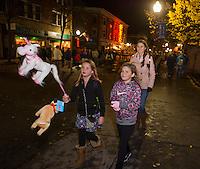 Bella Jenna and Nyla Shosa walk their unicorn and dog down Main Street with Sarah Jenna during Pumpkin Fest Saturday evening.  (Karen Bobotas/for the Laconia Daily Sun)