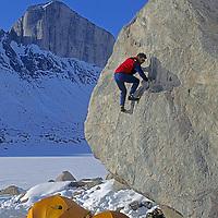 BAFFIN ISLAND, NUNAVUT, CANADA. Greg Child (MR) bouldering at base camp during big wall climbing expedition to Great Sail Peak.