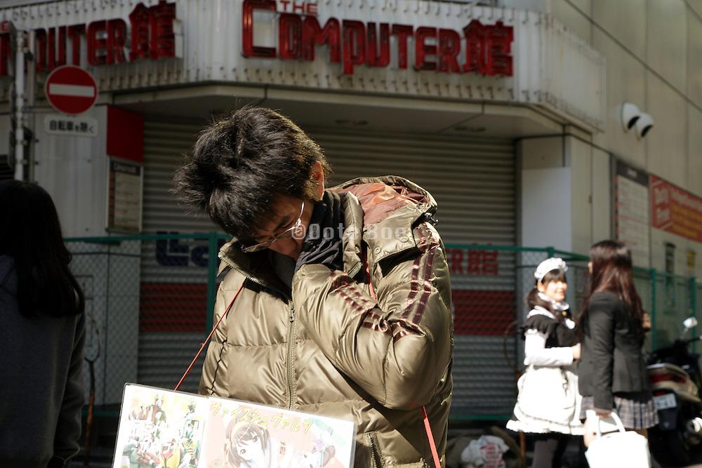 boy with a maid cafe billboard in Akihabara Tokyo