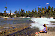 Girl watching cascade from the banks of the Tuolumne River, Tuolumne Meadows area, Yosemite National Park, California