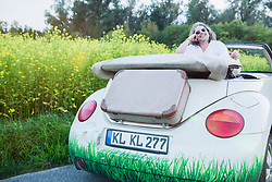 Happy man sitting in a car Beetle Cabrio looking back, Bavaria, Germany