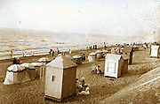 French coastal scene with people on a beach. Circa 1900
