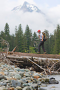 Climber Chris Moorehead carries his mountain bike over the South Fork Sauk River on the way towards Monte Cristo Townsite in Mount Baker-Snoqualmie National Forest, Washington.