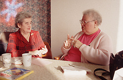 Two elderly women with hearing impairments using sign language to communicate,