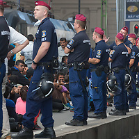 Line of riot police oversees illegal migrants sitting on the platform to prevent them having any accident as they wait to board a train in hopes to leave for Germany at the main railway station Keleti in Budapest, Hungary on September 03, 2015. ATTILA VOLGYI