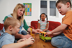 Nursery nurse with children playing with toys