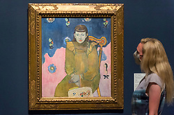 """© Licensed to London News Pictures. 04/08/2020. LONDON, UK. A staff member poses with """"Portrait of a Young Girl (Vaite 'Jeanne' Goupi')"""", 1896, by Paul Gauguin.  Preview of """"Gauguin and the Impressionists : Masterpieces from the Ordrupgaard Collection"""" at the Royal Academy of Arts in Piccadilly.  60 works from a collection of Impressionist paintings, assembled by wealthy Danish couple Wilhelm and Henny Hansen, are on show 7 August to 18 October 2020, and includes masterpieces by Gauguin, Degas, Monet, Morisot, Pissarro, Renoir and Sisley.  Photo credit: Stephen Chung/LNP"""