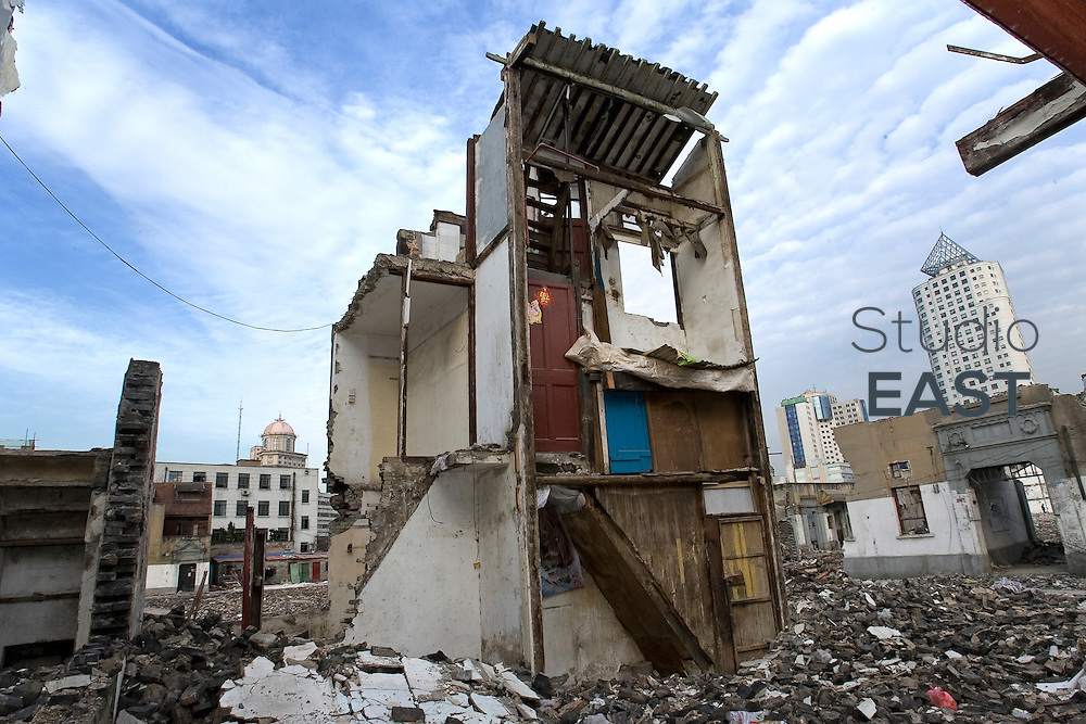 The remains of a house stand in an old neighborhood in the process of being demolished to make way to more modern residences, in Shanghai, China, on April 2, 2010. Photo by Lucas Schifres/Pictobank
