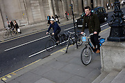 Cyclists on both road and pavement with two bicycles locked to posts on opposite sides of the road outside the Bank of England in the City of London.