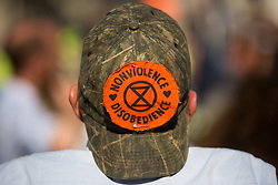 A climate activist wearing an Extinction Rebellion badge on a baseball cap sits in the road in front of the Bank of England on the eleventh day of Impossible Rebellion protests on 2nd September 2021 in London, United Kingdom. The activists, who had marched from the Tate Modern, included over fifty wearing signs indicating that they were breaking restrictive bail conditions by entering the City of London. Extinction Rebellion are calling on the UK government to cease all new fossil fuel investment with immediate effect.