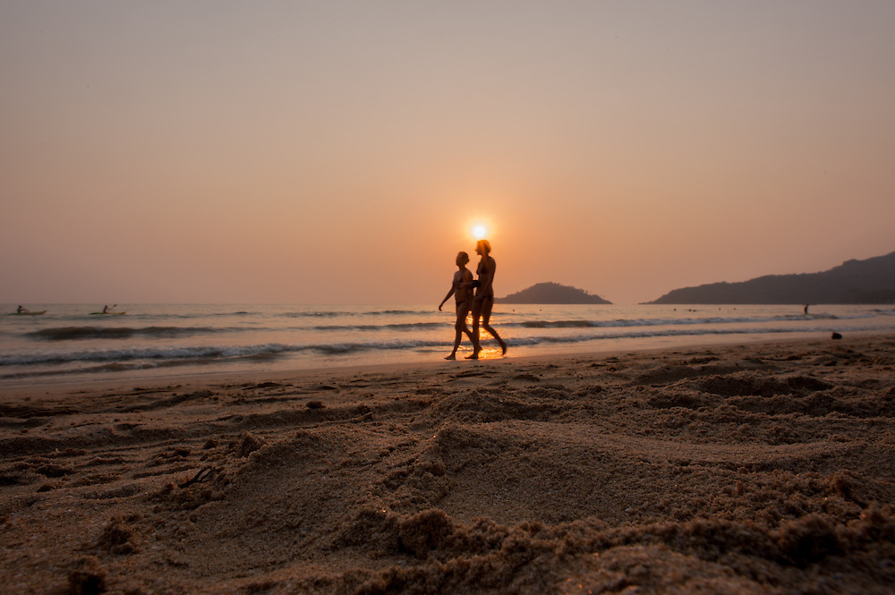 Couple walking on the beach at sunset in Goa (India)