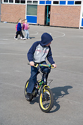 Young boy riding bicycle in school playground,
