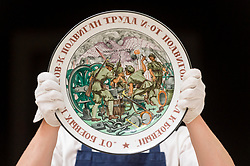 """© Licensed to London News Pictures. 31/05/2019. LONDON, UK. A technician presents """"Feats of Labour"""", a Soviet porcelain platter made in the State Porcelain Factory, circa 1921 (Est. GBP 30,000-50,000) at a preview of works from the upcoming sale of Russian Pictures, Works of Art, Fabergé & Icons Sales at Sotheby's, New Bond Street, on 4 June 2019.  Photo credit: Stephen Chung/LNP"""
