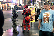Two people dressed as robots are standing along Hollywood Boulevard, in central Los Angeles, California, USA.