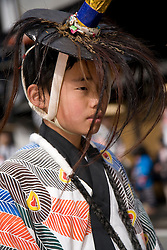 Asia, Japan, Gifu prefecture, Takayama (also known as Hida-Takayama), male teenager in traditional robe and hat walks in Gonjunko Procession during Sanno Festival of Hie Jinja Shrine, held annually in April.
