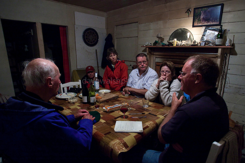 Visitors having wine and cheese around the table with farmer and conservationist Geoff King Kingsrun, near Arthur River, in north west Tasmania. Geoff has let some of his seafront land turn wild in order to promote wildlife. Several times a month he takes a group of people to an old fishing shack on the shore, where he serves them with wine, cheese, yarns - and a devil's restaurant. Geoff places a dead wallaby outside the hut, and using baby monitors to alert the watchers and spotlights to illuminate the nocturnal tasmanian devils, the visitors can see real, wild, Tasmanian devils. The contagious cancer, DFTD has penetrated many parts of Tasmania, but this corner has as of yet been kept clear of it.
