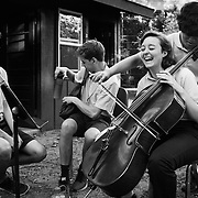 World Youth Symphony Orchestra students Joseph lee, 18, of California, right, attempts to play a melody on cello using the bow of Anna Seppa, 17, of Washington, center, while practicing in the practice huts at Interlochen Center for the Arts in Interlochen, Michigan.