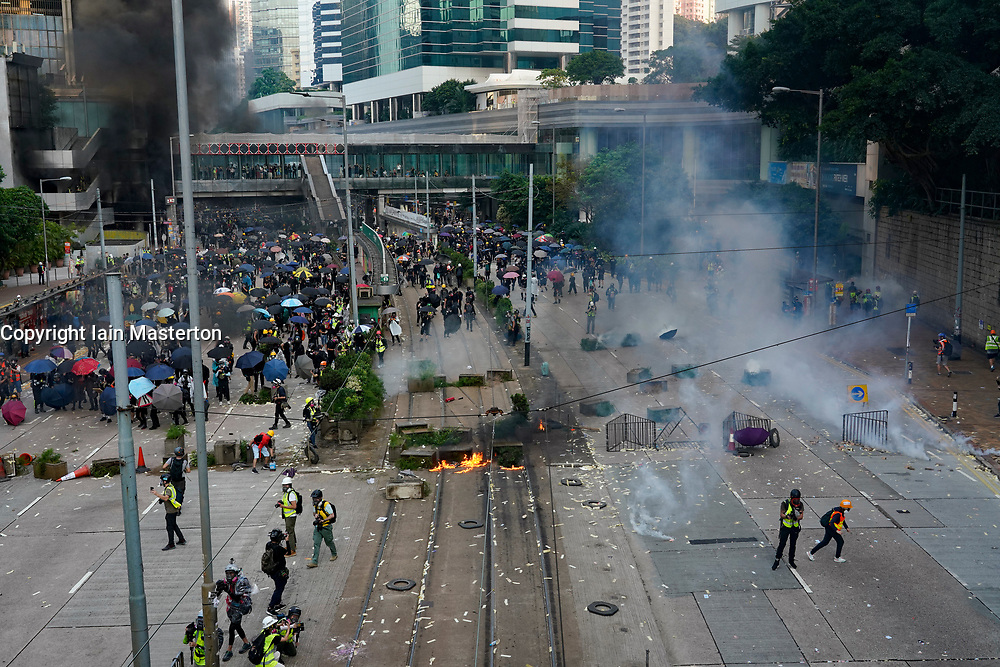 Hong Kong. 1 October 2019. After a peaceful march through Hong Kong Island by an estimated 100,000 pro democracy supporters, violent flared up at Tamar, Admiralty and moved through Wanchai district. Police used teargas and baton rounds and water cannon. Hard core group lit fires, threw bricks and Molotov cocktails at police. Violence continues into evening. Protestors on streets at Admiralty attacked by riot police using teargas. Iain Masterton/Alamy Live News.