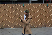 A young woman with some paperwork in her mouth walks past the zigzag battens of a construction hoarding at Notting Hill, on 13th March 2018, in London, England.