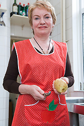 Cook peeling potatoes in kitchen of Polish Social Club,