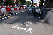 Social distancing signs painted onto the pavement in Moseley due to the Coronavirus pandemic, on 3rd August 2020 in Birmingham, United Kingdom. Coronavirus or Covid-19 is a respiratory illness that has not previously been seen in humans. While much or Europe has been placed into lockdown, the UK government has put in place more stringent rules as part of their long term strategy, and in particular social distancing.