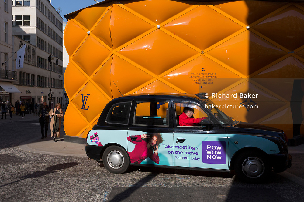 A black cab with advertising for PowWowNow, the instant conference calling service drives past the temporary renovation hoarding of luxury brand Louis Vuitton in New Bond Street, on 25th February 2019, in London, England.