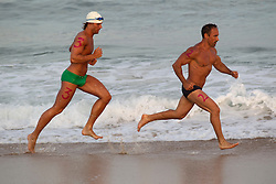 two tri-athletes running along the shore of the beach in East Hampton