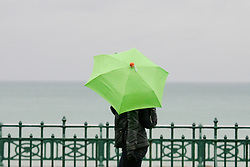 © under license to London News Pictures. 12/06/12. Heavy rainfall across the south east, a woman walks along Brighton seafront. The met office has issued severe weather warnings in England and Wales. Unseasonal weather in the south east has caused flooding. Sussex has been badly hit. Brighton XAVIER ITTER/LNP