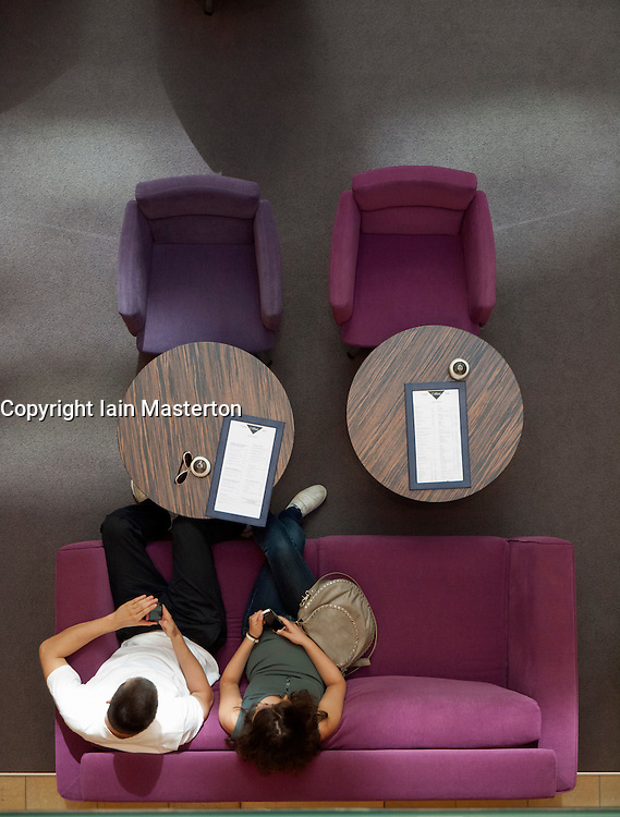 Couple using mobile phones on colorful sofa inside atrium of upmarket shopping mall on Friedrichstrasse in Berlin Germany