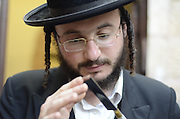 Kosher Chicken slaughter by a Shohet of the ultra religious Neturei Kata sect, Jerusalem, Israel Checking the blade for imperfections