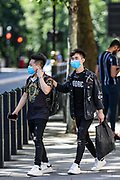 People are seen wearing face protective masks in Central London, on Monday, June 22, 2020. The two-metre social distancing rule will be under review as the UK relax coronavirus lockdown measures implemented to stem the spread of the virus. The UK's coronavirus death toll has passed more than 40,000, according to the latest government figures. A total of 40,261 people have died in hospitals, care homes and the wider community after testing positive for the virus. (Photo/ Vudi Xhymshiti)
