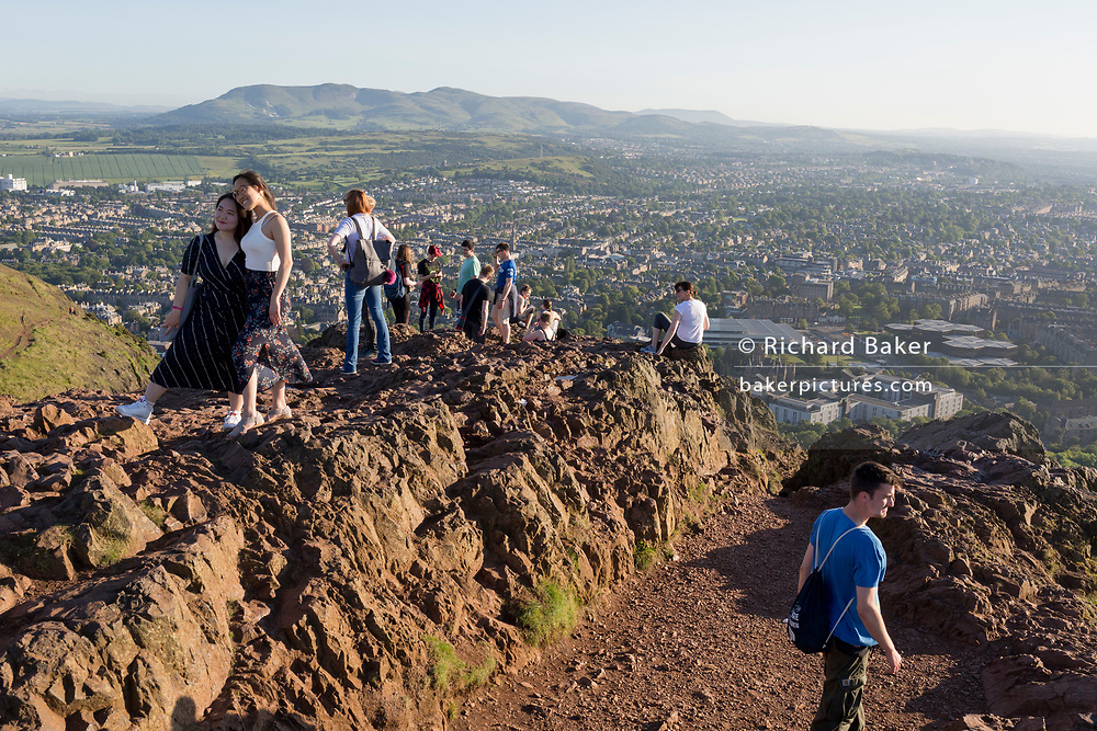 "Walkers enjoy summer evening sunshine on the summit of Arthur's Seat in Holyrood Park, overlooking the city of Edinburgh, on 26th June 2019, in Edinburgh, Scotland. Arthur's Seat is an extinct volcano which is considered the main peak of the group of hills in Edinburgh, Scotland, which form most of Holyrood Park, described by Robert Louis Stevenson as ""a hill for magnitude, a mountain in virtue of its bold design"". The hill rises above the city to a height of 250.5 m (822 ft), providing excellent panoramic views of the city and beyond."