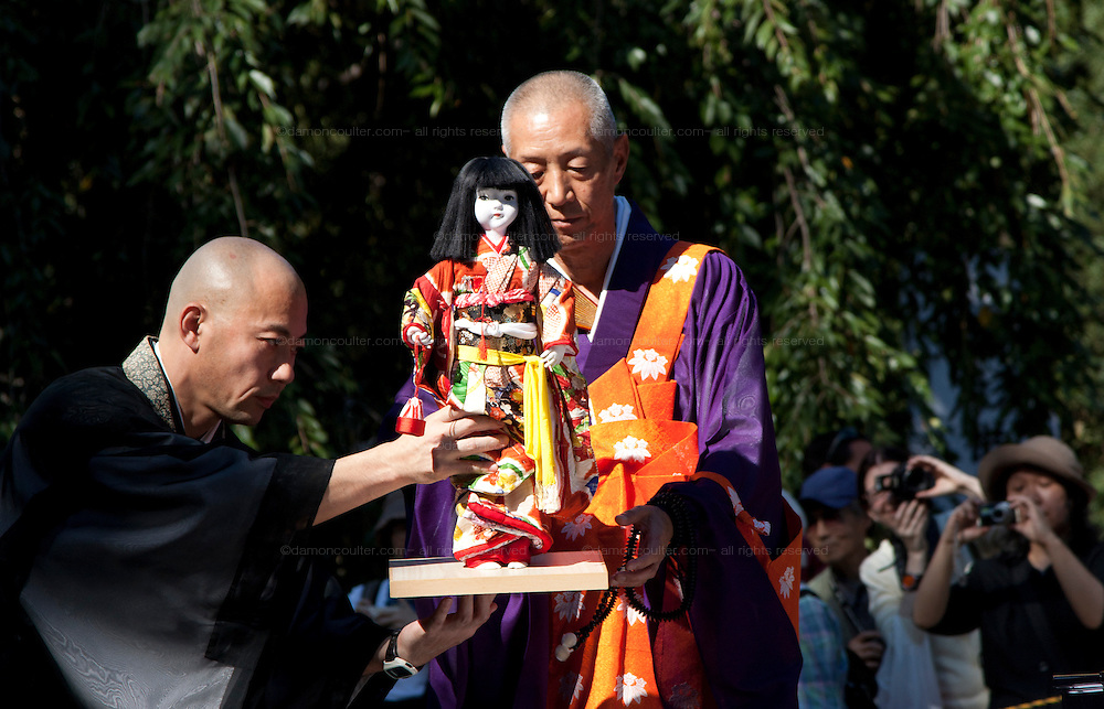 A Monk hands a doll to another festival official at the Ningyo Kuyo matsuri or festival of last rights for the memory of beloved, old dolls in Kiyomizu Kannon-do Temple in Ueno Park, Tokyo, Japan September 25th 2009