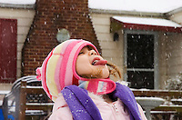 child age 3 catches snowflakes on her tongue